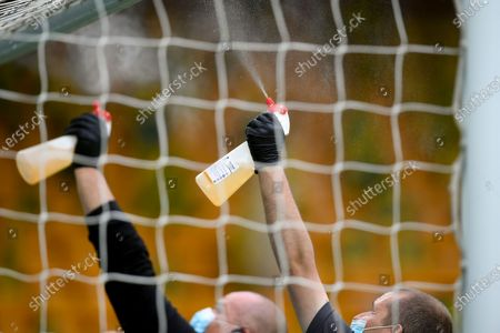 Staff members disinfect the goal bar during the English FA Cup quarter final soccer match between Norwich City and Manchester United in Norwich, Britain, 27 June 2020.