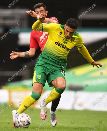 Ben Godfrey (front) of Norwich in action against Bruno Fernandes (back) of Manchester United during the English FA Cup quarter final soccer match between Norwich City and Manchester United in Norwich, Britain, 27 June 2020.