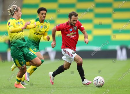 Juan Mata (R) of Manchester United in action against Norwich players Todd Cantwell (L) and Jamal Lewis (C) during the English FA Cup quarter final soccer match between Norwich City and Manchester United in Norwich, Britain, 27 June 2020.