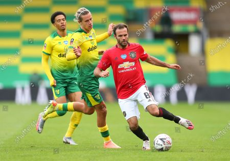 Juan Mata (R) of Manchester United in action against Norwich players Todd Cantwell (C) and Jamal Lewis (L) during the English FA Cup quarter final soccer match between Norwich City and Manchester United in Norwich, Britain, 27 June 2020.