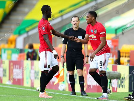 Anthony Martial (R) of Manchester United replaces his teammate Eric Bailly (L) during the English FA Cup quarter final soccer match between Norwich City and Manchester United in Norwich, Britain, 27 June 2020.