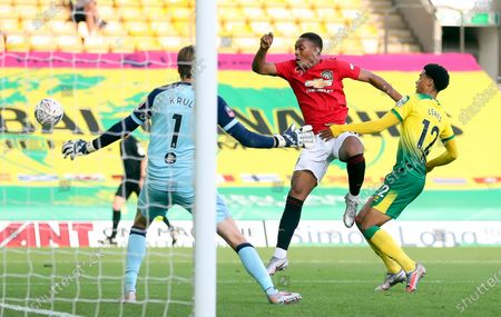 Anthony Martial (C) of Manchester United in action against Norwich players Jamal Lewis (R) and goalkeeper Tim Krul (L) during the English FA Cup quarter final soccer match between Norwich City and Manchester United in Norwich, Britain, 27 June 2020.