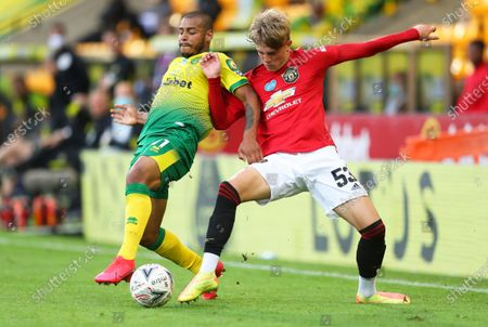Brandon Williams (R) of Manchester United in action against Onel Hernandez (L) of Norwich during the English FA Cup quarter final soccer match between Norwich City and Manchester United in Norwich, Britain, 27 June 2020.