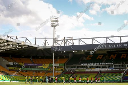 Players of Norwich (front) and Manchester United (back) observe a minute of silence for the victims of the coronavirus COVID-19 pandemic in front of empty stands at Carrow Road Stadium prior to the English FA Cup quarter final soccer match between Norwich City and Manchester United in Norwich, Britain, 27 June 2020.