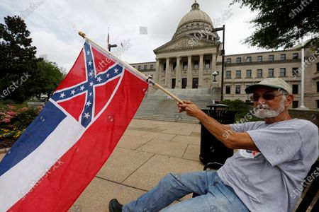 Larry Eubanks of Star waves the current Mississippi state flag as he sits before the front of the Capitol, in Jackson, Miss. While a supporter of the current flag, Eubanks says he would hope lawmakers would allow a proposed flag change to be decided by the registered voters. The current state flag has in the canton portion of the banner the design of the Civil War-era Confederate battle flag, that has been the center of a long-simmering debate about its removal or replacement
