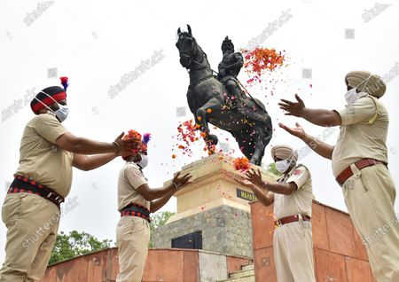 Stock Image of Punjab Police personnel release flower petals while paying their tribute to Maharaja Ranjit Singh on his death anniversary at his memorial, in Ram Bagh garden, on June 27, 2020 in Amritsar, Punjab, India. Maharaja Ranjit Singh was the leader of the Sikh Empire, which ruled the northwest Indian subcontinent in the early half of the 19th century. He survived smallpox in infancy but lost sight in his left eye. He was born in Gujranwala (now in Pakistan) on November 13, 1780, and died on June 27, 1839, in Lahore.