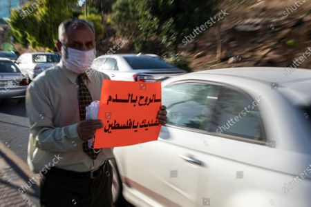 A protester wears a face mask as he holds up a banner reading in Arabic: 'With our souls we will protect you, oh Palestine' during a protest against Israel's plans to imminently annex parts of the occupied West Bank and the Jordan valley, in Amman, Jordan, 27 June 2020. The Israeli government is gearing up to annex land in what it sees as the provinces of Judea and Samaria occupied since the 1967 Six-Day war. The annexation of up to 30 percent of the occupied Palestinian territory, deemed illegal under extant international law, would fulfill a campaign promise pledged by Israeli Prime Minister Benjamin Netanyahu during the recent general elections. The move has the full backing of the administration of US President Donald J. Trump - which expressed its support for what it described as 'The Deal of the Century' back in January - but is overwhelmingly rejected by most actors in the restive region.