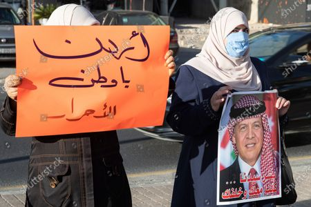 Stock Picture of Two female protesters hold up a placard reading in Arabic: 'Oh Jordan, land of free men' (L) and a portrait of Jordanian King Abdullah II (R) during a protest against Israel's plans to imminently annex parts of the occupied West Bank and the Jordan valley, in Amman, Jordan, 27 June 2020. The Israeli government is gearing up to annex land in what it sees as the provinces of Judea and Samaria occupied since the 1967 Six-Day war. The annexation of up to 30 percent of the occupied Palestinian territory, deemed illegal under extant international law, would fulfill a campaign promise pledged by Israeli Prime Minister Benjamin Netanyahu during the recent general elections. The move has the full backing of the administration of US President Donald J. Trump - which expressed its support for what it described as 'The Deal of the Century' back in January - but is overwhelmingly rejected by most actors in the restive region.