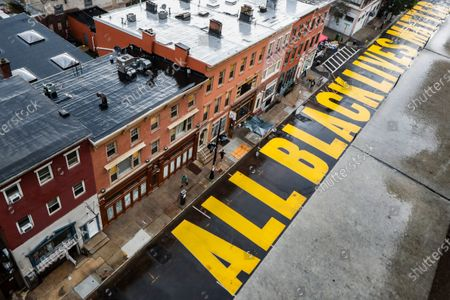 "Pedestrians pass a mural that reads ""ALL BLACK LIVES MATTER"" painted on Halsey Street, in Newark, N.J"