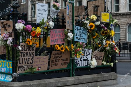Flowers and placards are left attached to the railings at Westminster tube station after thousands of transgender people and their supporters marched through central London to celebrate the Black trans community, commemorate the Black trans lives lost and protest against potential changes to the Gender Recognition Act.