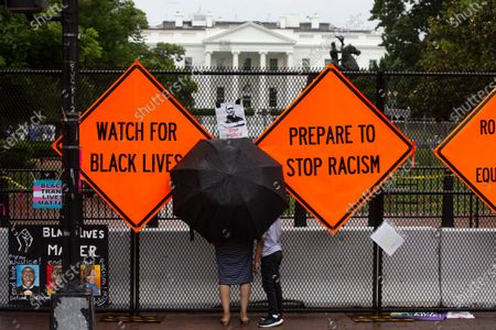A woman and a child stand under an umbrella beside signs placed by Black Lives Matter supporters, including one depicting George Floyd, on the fence on the north side of Lafayette Park across the street from the White House in Washington, DC, USA, 27 June 2020. Temporary fencing around the park had been taken down but was put back up after clashes between police and protesters that tried to take down the Andrew Jackson statue in Lafayette Park, 22 June. The death of George Floyd while in Minneapolis police custody has sparked protests demanding policing reform and racial equality.