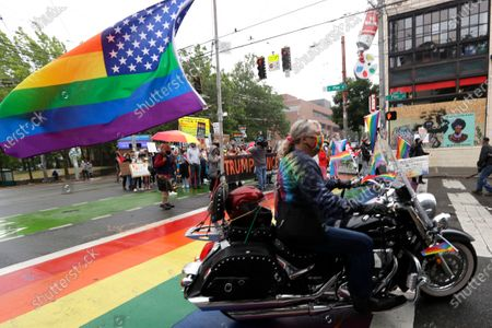 Aubrey Thomas is the lone representatives of Dykes on Bikes as she leads an LGBTQ Pride march over a rainbow-painted crosswalk and heads toward an area where streets are blocked off in what has been named the Capitol Hill Occupied Protest zone to show solidarity with protesters, in Seattle. The march of about 200 came with most LGBTQ Pride weekend events replaced with virtual events because of the coronavirus outbreak. Marchers demonstrated in solidarity with the community in remembering the death of George Floyd, and against police abuse and excessive force
