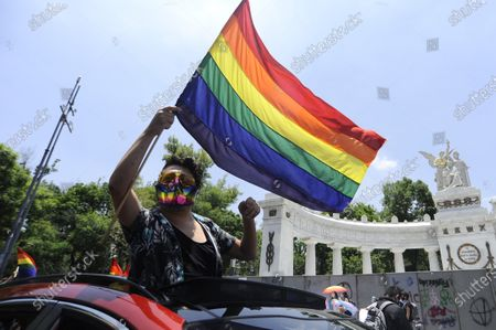 A member of LGBT holds a Rainbow flag while joins  a reduced Pride March to celebrate the  42th birthday by marching through the streets of Mexico. They holding a LGBTQ+ pride parade and protest for their rights amid of the new coronavirus pandemic.