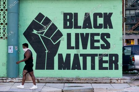 Stock Image of A pedestrian walks past a Black Lives Matter mural in Washington, DC, USA, 27 June 2020. The death of George Floyd, while in Minneapolis police custody, has sparked protests demanding policing reform and racial equality.