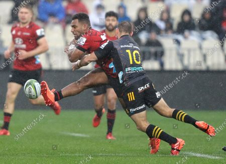 Crusaders Sevu Reece kicks the ball as he is tackled by Chiefs Aaron Cruden during the Super Rugby Aotearoa rugby game between the Crusaders and Chiefs in Christchurch, New Zealand