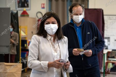 Stock Picture of The incumbent mayor of Paris, Anne Hidalgo (L) with her husband Jean-Marc Germain (R) vote in the second round of the mayoral elections, in Paris, France, 28 June 2020. The second round of municipal elections was to be held on 22 March 2020 but was delayed due to the spread of the coronavirus pandemic causing the Covid-19 disease.