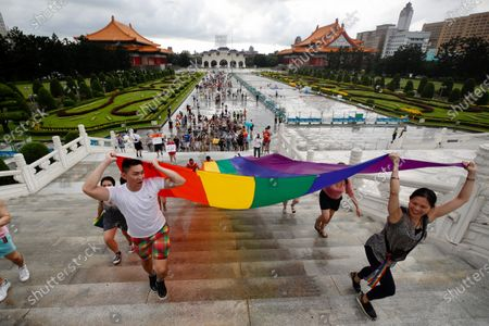 Members of the LGBT community hoist a rainbow flag as they march to celebrate the Pride month at the National Chiang Kai-shek Memorial Hall in Taipei, Taiwan, 28 June 2020. Due to the coronavirus pandemic, Taiwan is one of the few countries to hold this year's 50th anniversary Pride March.