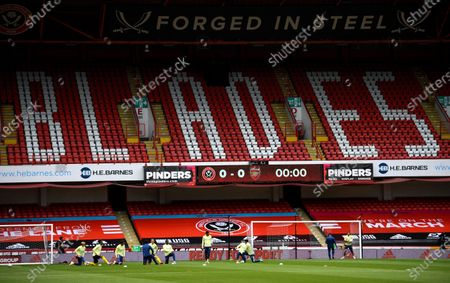 Arsenal's players warm up in front of the empty tribunes prior the English FA Cup quarter final match between Sheffield United and Arsenal London in Sheffield, Britain, 28 June 2020.
