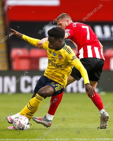 Bukayo Saka (L) of Arsenal in action against John Lundstram (R) of Sheffield during the English FA Cup quarter final match between Sheffield United and Arsenal London in Sheffield, Britain, 28 June 2020.