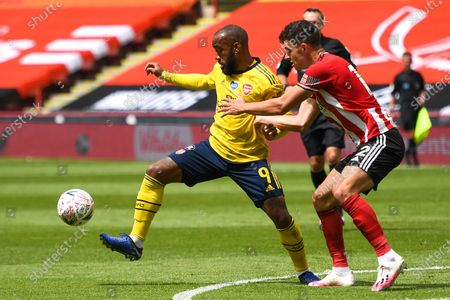 Arsenal's Alexandre Lacazette (L) in action against George Baldock (R) of Sheffield during the English FA Cup quarter final match between Sheffield United and Arsenal London in Sheffield, Britain, 28 June 2020.