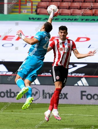 Arsenal's goalkeeper Emiliano Martinez (L) in action against Sheffield United's John Egan (R) during the English FA Cup quarter final soccer match between Sheffield United and Arsenal FC in Sheffield, Britain, 28 June 2020.