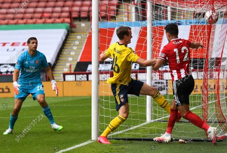 John Egan (R) of Sheffield in action against Rob Holding (C) of Arsenal during the English FA Cup quarter final soccer match between Sheffield United and Arsenal FC in Sheffield, Britain, 28 June 2020.