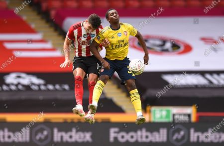 Sheffield United's John Egan (L) in action against Arsenal's Eddie Nketiahl (R) during the English FA Cup quarter final soccer match between Sheffield United and Arsenal FC in Sheffield, Britain, 28 June 2020.