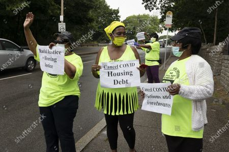 Annie Gordon, left, Gabrielle Rene, center, and Jenny Clark, right, rally for protection from evictions, in the Mattapan neighborhood of Boston. Massachusetts' tenant eviction moratorium is slated to expire in mid-August