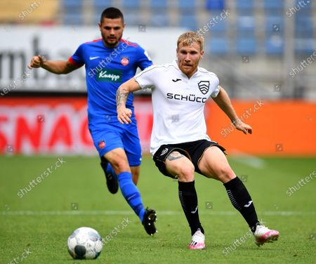 Marnon Busch (L) of Heidenheim in action against Andreas Voglsammer (R) of Bielefeld during the German Bundesliga Second Division soccer match between DSC Arminia Bielefeld and FC Heidenheim 1846 in Bielefeld, Germany, 28 June 2020.