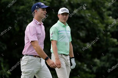 Kevin Streelman, left, walks with Mackenzie Hughes, of Canada, after teeing off on the 13th hole during the final round of the Travelers Championship golf tournament at TPC River Highlands, in Cromwell, Conn