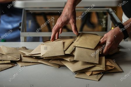 An official takes out the ballots from a ballot box and prepares them for volunteers to count them at a polling station in the city hall of the 14th district during the second round of the French Municipal elections in Paris, France, 28 June 2020. The 2020 French municipal elections are held from 15 March to 28 June to renew the municipal councils for almost 35,000 French communes by choosing all of its mayors and other local leaders, The first round took place on 15 March but the second round has been postponed to 28 June, due to the Covid-19 coronavirus pandemic.