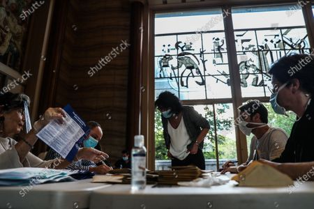 Volunteers wearing face masks count ballots at a polling station in the city hall of the 14th district during the second round of the French Municipal elections in Paris, France, 28 June 2020. The 2020 French municipal elections are held from 15 March to 28 June to renew the municipal councils for almost 35,000 French communes by choosing all of its mayors and other local leaders, The first round took place on 15 March but the second round has been postponed to 28 June, due to the Covid-19 coronavirus pandemic.