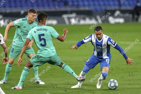 Espanyol's Raul de Tomas, right, duels for the ball against Real Madrid's Raphael Varane during the Spanish La Liga soccer match between RCD Espanyol and Real Madrid at the Cornella-El Prat stadium in Barcelona, Spain
