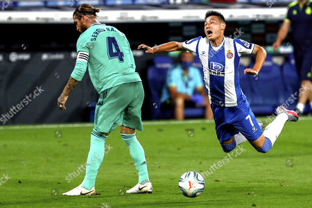 Espanyol's Wu Lei, right, is tackled by Real Madrid's Sergio Ramos during the Spanish La Liga soccer match between RCD Espanyol and Real Madrid at the Cornella-El Prat stadium in Barcelona, Spain