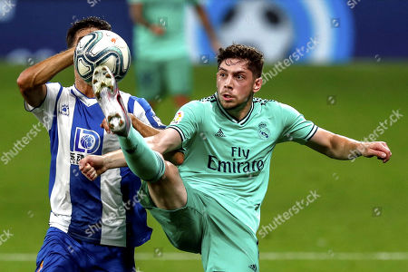 Real Madrid's Federico Valverde, right, duels for the ball against Espanyol's Didac Vila during the Spanish La Liga soccer match between RCD Espanyol and Real Madrid at the Cornella-El Prat stadium in Barcelona, Spain