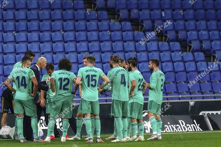 Real Madrid's head coach Zinedine Zidane talks to Real Madrid players during the Spanish La Liga soccer match against RCD Espanyol at the Cornella-El Prat stadium in Barcelona, Spain