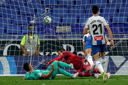 Real Madrid's Casemiro, left, scores the opening goal during the Spanish La Liga soccer match between RCD Espanyol and Real Madrid at the Cornella-El Prat stadium in Barcelona, Spain