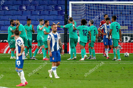 Real Madrid players, background, celebrate after scoring the opening goal during the Spanish La Liga soccer match between RCD Espanyol and Real Madrid at the Cornella-El Prat stadium in Barcelona, Spain