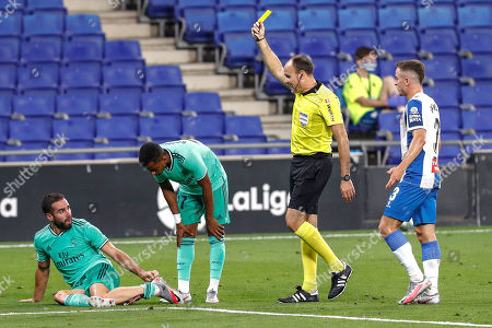 Referee Mateu Lahoz shows a yellow card to Espanyol's Adria Pedrosa, right, during the Spanish La Liga soccer match between RCD Espanyol and Real Madrid at the Cornella-El Prat stadium in Barcelona, Spain