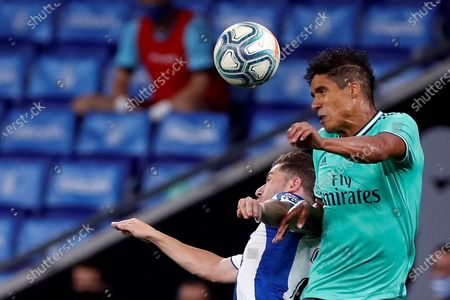 Stock Photo of Real Madrid's Raphael Varane (R) in action against Adrian Embarba (L) of RCD Espanyol during the Spanish LaLiga soccer match between RCD Espanyol and Real Madrid held at RCDE Stadium, in Barcelona, Spain, 28 June 2020.
