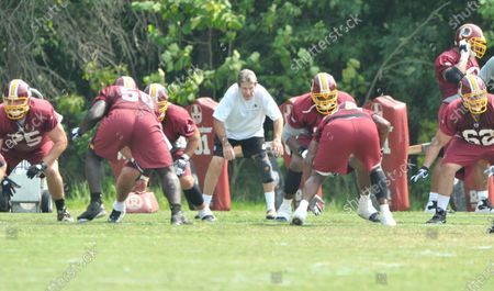 Stock obrázek na téma Ashburn, VA - -- Offensive Line Coach Joe Bugel (in white) puts his players through some drills during the 2009 Washington Redskins Training Camp at Redskins Park in Ashburn, Virginia..