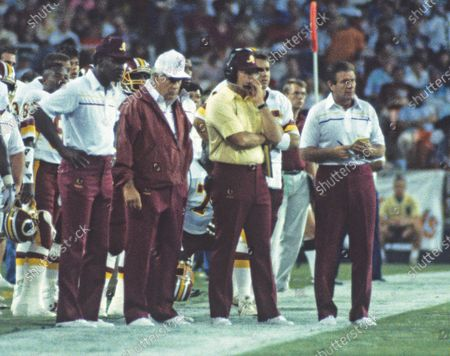 Washington Redskins coaches watch the game action from the sidelines during pre-season game against the Miami Dolphins at RFK Stadium in Washington, D.C.. From left to right: Charley Taylor, Don Breaux, Joe Gibbs, quarterback Stan Humphries, and Joe Bugel. The Redskins won the game 35 - 21.
