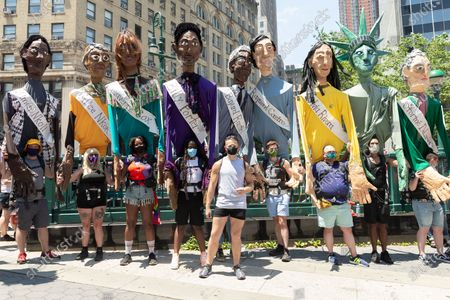 Atmosphere at queer liberation march and rally for black lives and against police brutality at Foley Square and Chambers street. Pride parade was cancel this year because of COVID-19 pandemic. Gay and transgender people gather for march and rally to celebrate 50th anniversary of Stonewall uprising and in support of Black LIves Matter movement. Pride Puppets seen by artist Chris Williams who created some puppets in the likes of Marsha P. Johnson, Sylvia Rivera, Billy Porter, Laverne Cox, Janelle Monae. Chris poses in the middle.