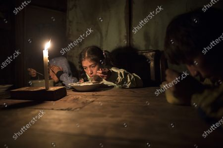 Stock Image of Siblings Estiben Aquiño, 4, Estefany Aquino, 11, and Javier Aquino, 14, eat dinner illuminated by a candle in their home in the Nueva Esperanza neighborhood that has no access to electricity, in Lima, Peru