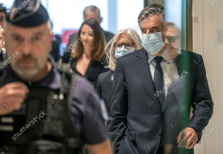 France's former Prime Minister Francois Fillon, right, and his wife Penelope wear protective masks as they arrive at Paris courthouse, in Paris, . A Paris court is set to render or postpone a verdict in the fraud trial of former Prime Minister Francois Fillon on Monday