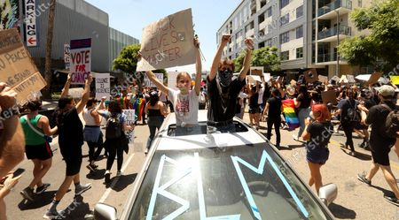 HOLLYWOOD, CA - JUNE 14, 2020 - - Mari Kubani, left, and her boyfriend Zack Monterosso cheer while joining thousands participate in the All Black Lives Matter solidarity march to mark LGBTQ Pride Month along La Brea Ave. in Hollywood on June 14, 2020. The march also honored Tony McDade, a transgender man killed by Tallahassee Police Department officers on May 27. The march is in solidarity with the Black Lives Matter movement and highlight the contributions of people of color who were instrumental in organizing the LGBT movement, such as Marsha P. Johnson and Sylvia Rivera. The procession started on Hollywood Boulevard at Highland Avenue in Hollywood. (Genaro Molina / Los Angeles Times)