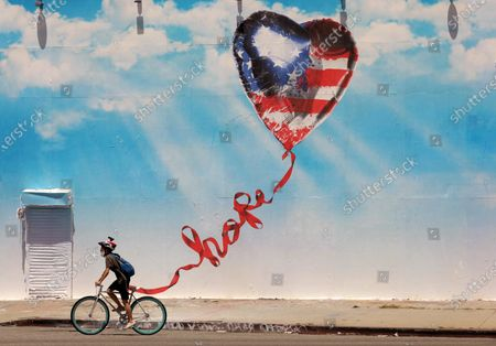 LOS ANGELES, CA - JUNE 15, 2020 - - A bicyclist rides past the latest mural created by Mr. Brainwash that tells Americans to remain hopeful in the time of the coronavirus pandemic in Los Angeles on June 15, 2020. (Genaro Molina / Los Angeles Times)