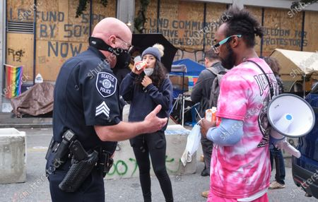 Acting Seattle police lieutenant Robert Brown (L) talks with a protestor in Capitol Hill Occupied Protest, an area near a precinct abandoned by police where activists continue to protest police brutality and support the Black Lives Matter movement, in Seattle, Washington, USA, 29 June 2020. Brown lead investigators from the Seatle Police Department to investigate the scene of a fatal shooting. The city is planning to remove barriers from the area and reoccupy the police station.