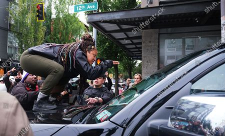 A protestor stand on the hood of a truck during a confontation with a FOX news television crew just outside the Capitol Hill Occupied Protest, an area near a precinct abandoned by police where activists continue to protest police brutality and support the Black Lives Matter movement, in Seattle, Washington, USA, 29 June 2020. The crew was forced to leave the area on foot.