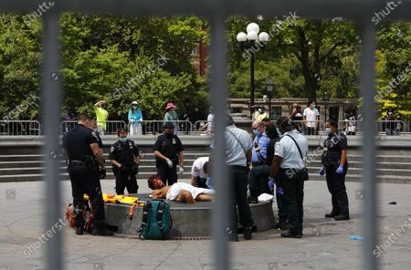 An autistic squatter Matthew Mishefksi of Wyoming, Pennsylvania (C) lays on the Washington Square Park fountain while being surrounded by members of the NYPD (New York City Police Department) and NYFD (New York Fire Department) in Washington Square Park in New York, New York, USA, 29 June 2020. Mishefski, who claims to be Jesus, has been squatting in the park since May and throughout the Black Lives Matter protests. He was arrested on 27 and 28 June for different reasons and released shortly after both arrests.